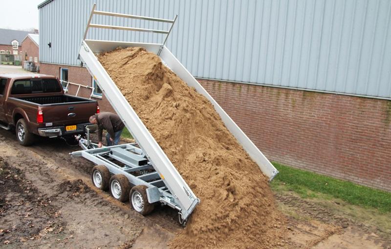 Разгрузка трехосного самосвального прицепа песка посредством ручного гидронасоса